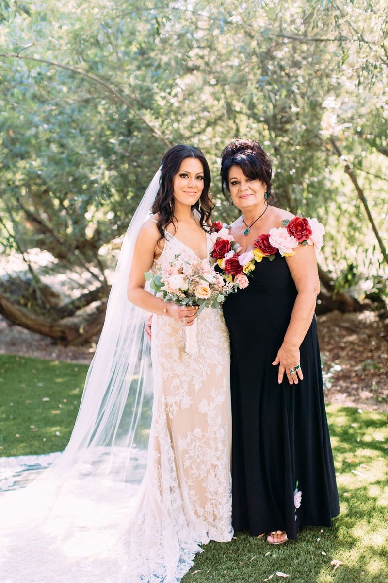 bride in calla blanche wedding dress with mother in black dress with faux flower neckline pink red