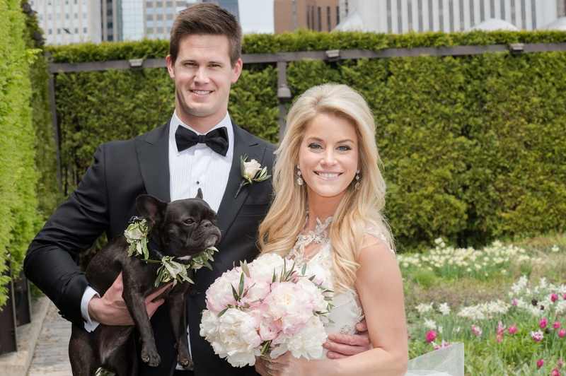 Bride with pink peony bouquet and groom in bow tie holding French bull dog with flower collar