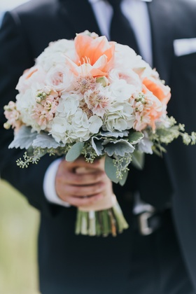 groom holding peach bridal bouquet with white hydrangeas, dusty miller, garden roses