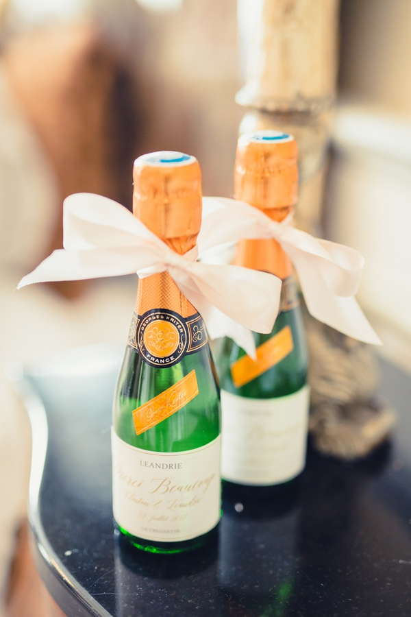 miniature champagne sparkling wine bottles with white ribbon for guests at place settings french