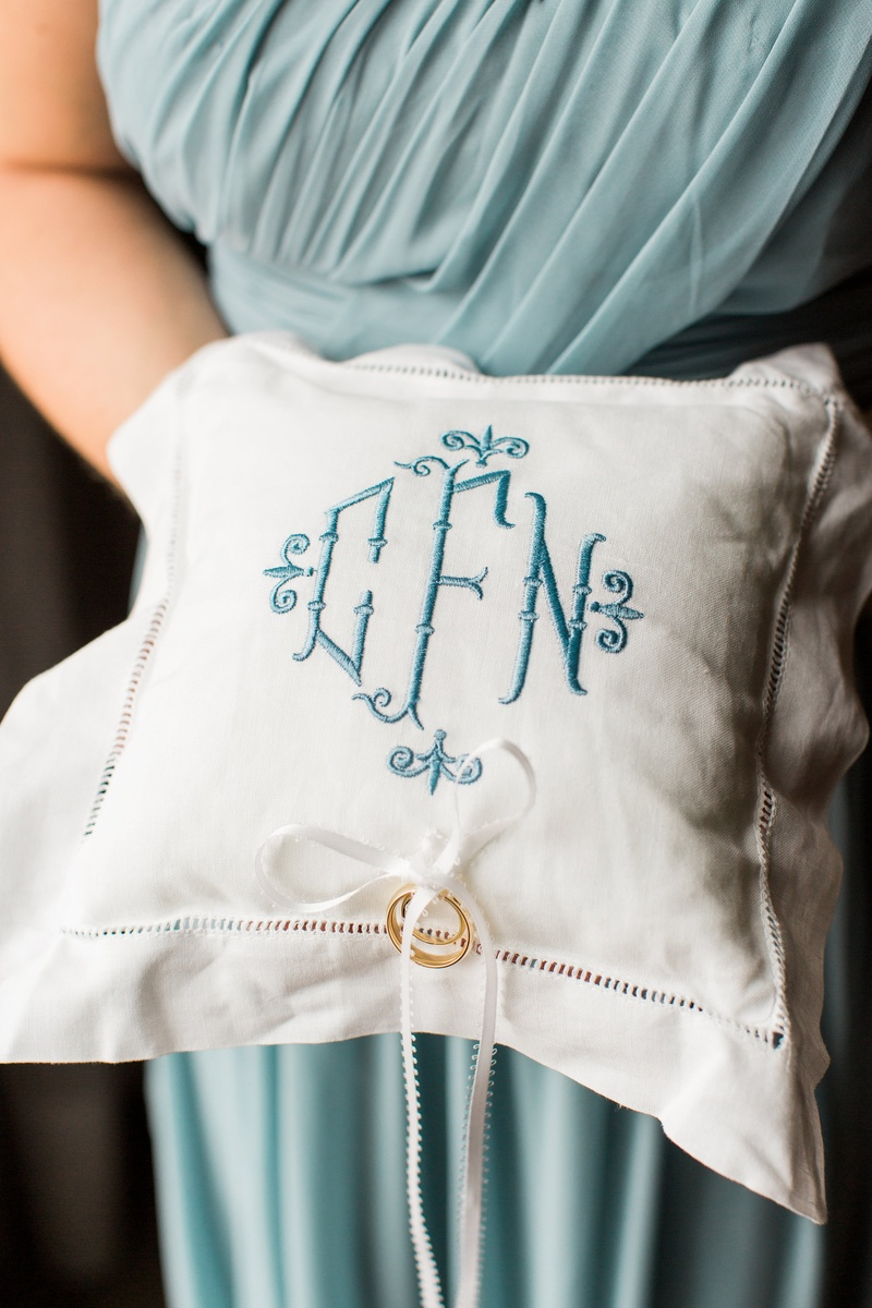 white ring pillow with blue embroidered monogram