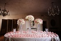 Pink escort cards on white oval table with tablecloth and tall arrangements with crystal vases