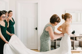 mother bridesmaids helping bride into dress long trail flowing rivini wedding gown green colors