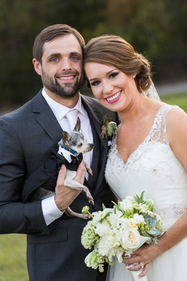 Bride in Nardos Iman wedding dress with rustic bouquet and groom in grey suit with little Chihuahua