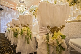 gold chair interlaces with yellow orchids, white roses, and green amaranths