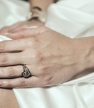 Close up picture of bride's hand with manicure and engagement ring