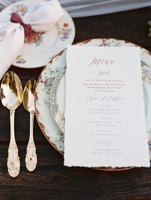 wedding menu on top of mismatched floral china with gold flatware