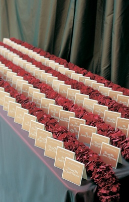 Tan place cards are divided by rows of red flowers