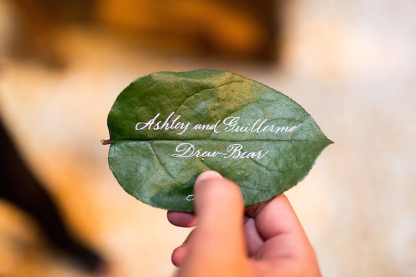 Wedding place card with white calligraphy on green leaves