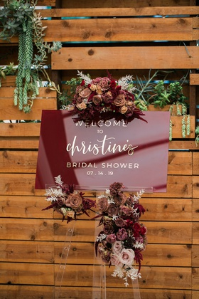 burgundy acrylic sign with gold lettering and flowers for bridal shower