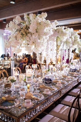 wedding reception long table with crystals in between top and bottom crystal charger mirror top