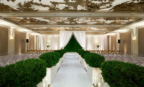wedding ceremony ballroom gold ceiling hedge along aisle hedge wall backdrop white drapery