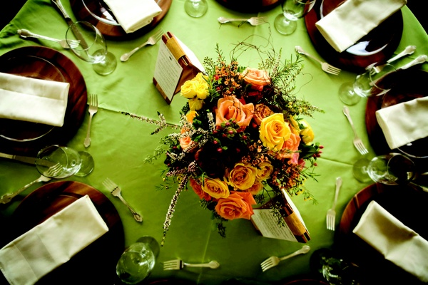 Wedding reception centerpiece of orange and yellow roses and greenery