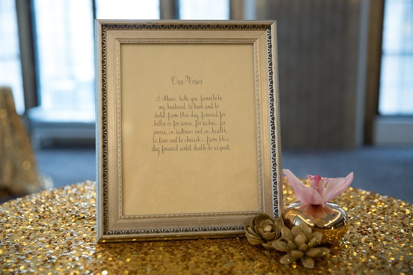 Handwritten vows framed in silver frame on gold sequin tablecloth