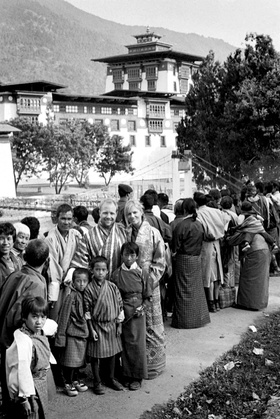 Black and white image of couple with Buddhist wedding guests in Bhutan