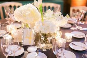 Low centerpiece with white roses, white hydrangeas, white calla lilies in separate vases