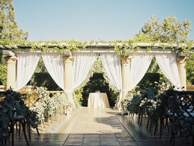 ceremony altar with columns, white drapery, greenery