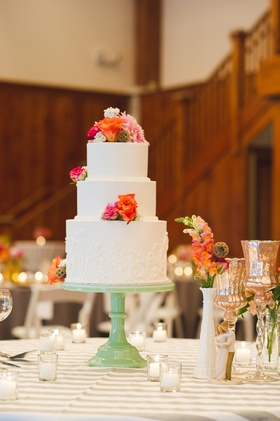white tiered cake with orange flowers on side and top