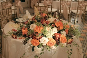 Couple's table with orange roses and greenery