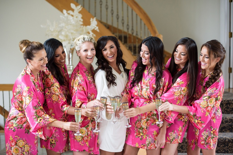 bride in white robe, bridesmaids in pink floral robes, bridal party champagne before wedding