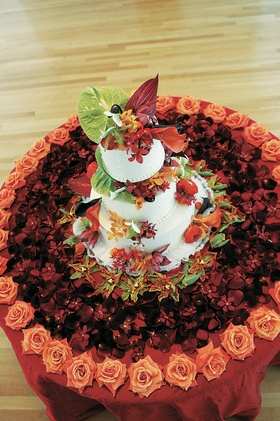 White cake with tropical flowers on flower covered cake table