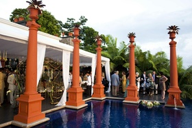 Guests mingling around orange pillars by pool