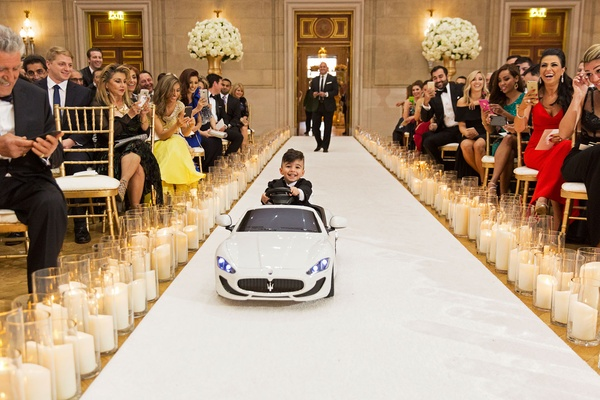 Wedding ceremony ring bearer driving down aisle in miniature maserati car candles guests