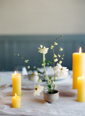 yellow pillar candles, mini pillar candles, ceramic bud vase with japanese ranunculus