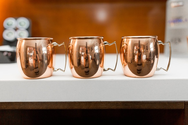 Wedding reception cocktail hour moscow mule copper mugs at wedding white bar