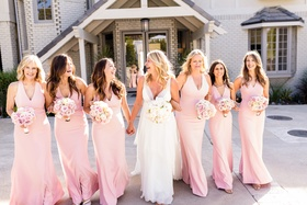 bride in christos v-neck wedding dress, bridesmaids in pink v-neck dresses from dessy