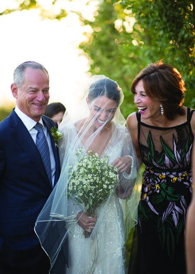bride with blusher veil laughing with her parents before walking down the aisle