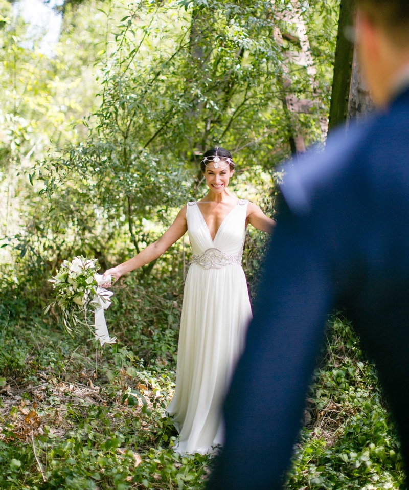 Back of groom's navy blue suit walking toward bride in forest v-neck wedding dress first look