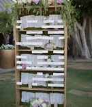Garden wedding reception with place cards displayed on bookcase with white, purple, peach flowers