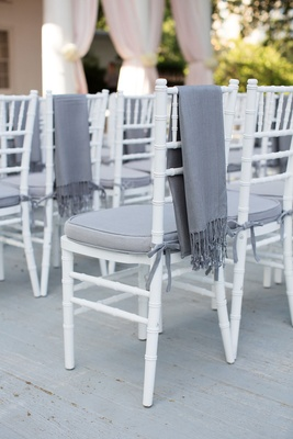 Guest chair with grey cushion and throw blanket for chilly weather outdoor wedding