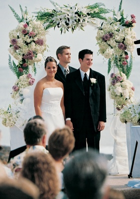 Oceanfront floral arch above newlyweds and officiant