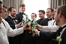 a groom and his groomsmen clad in black tuxedos toast to his upcoming marriage