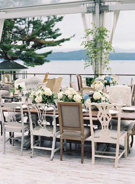 Antique seating chairs around wood tables without linens open side tent wedding reception by lake