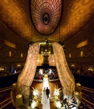 bride in julie vino wedding dress walking down aisle with dad tall ceiling gotham hall drapes lights
