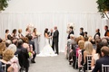 bride and groom saying vows against white fabric backdrop trumpet dress white and pink arrangements