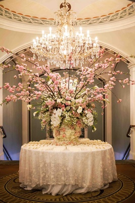 The Pierre wedding escort card table with pink branch arrangement