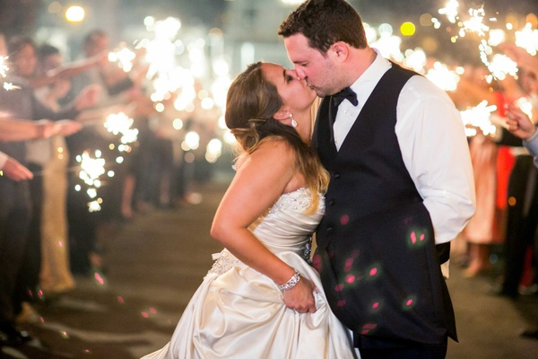 bride in allure ball gown, groom in navy joseph abboud suit kiss during sparkler exit