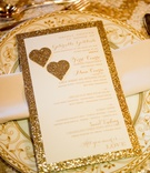 Wedding shower menu with golden glitter border and hearts on china chargers with florid pattern