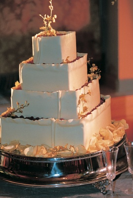 square white cake decorated with gold leaves