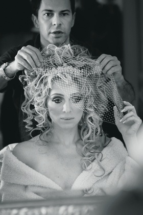 Black and white picture of bride wearing Toni Federici headpiece with birdcage veil