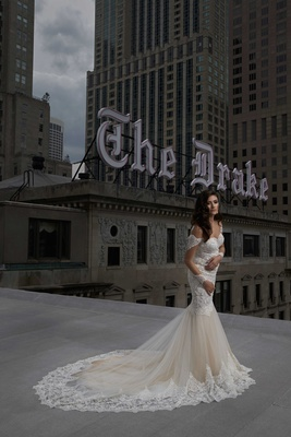 bride in lace trumpet dress long curled hair posing rooftop of the drake hotel chicago