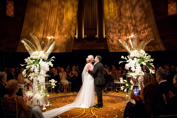 Bride and groom between calla lily orchid hydrangea rose gold palm flower arrangement in the round