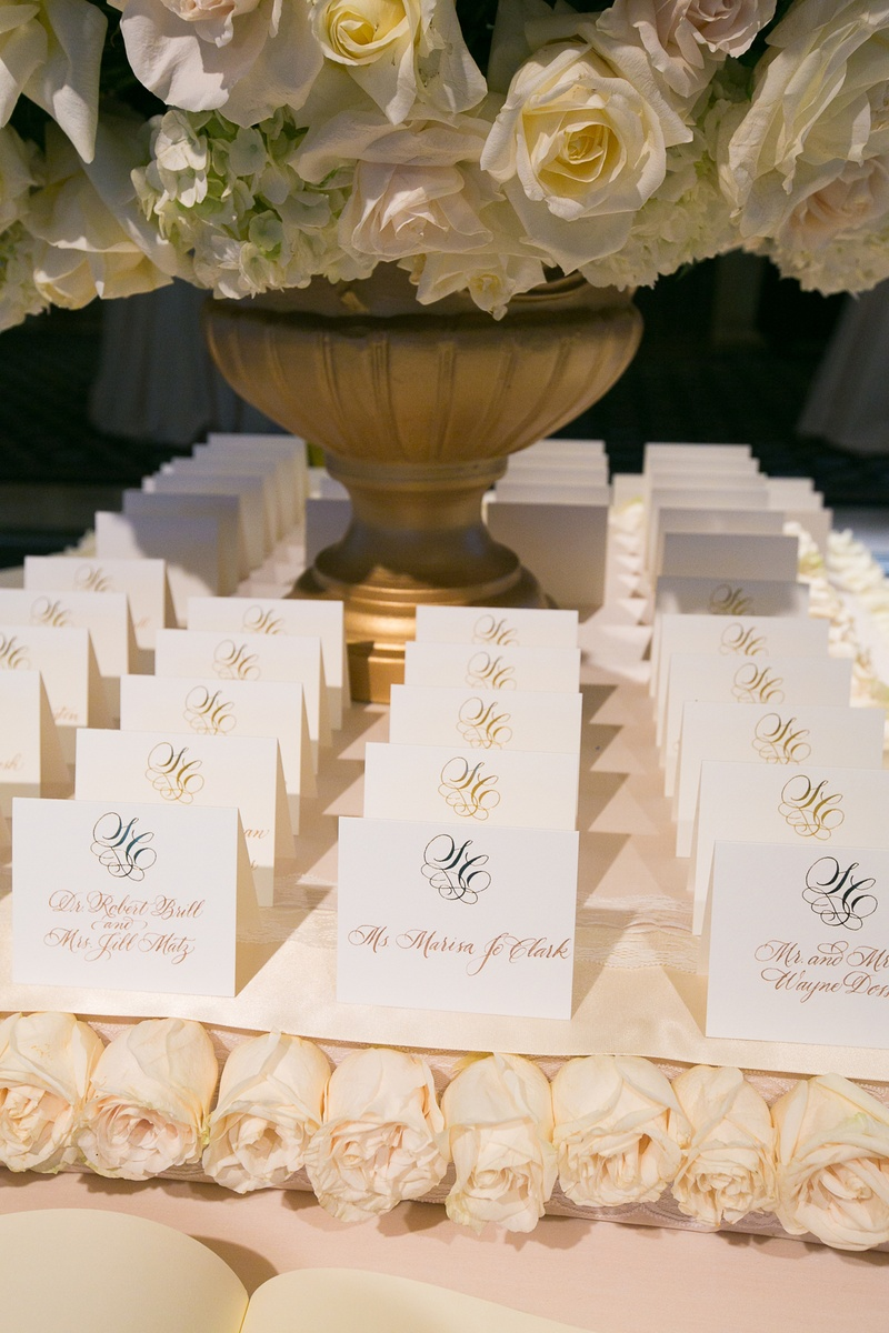 White seating cards with gold calligraphy on white roses