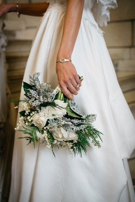 bride wearing mother's wedding dress and holding winter wedding bouquet white flowers greenery