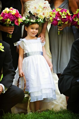 Flower girl in a white dress with grey sash