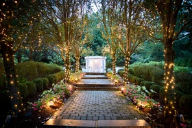 ashley alexiss wedding ceremony site outdoor venue lights on trees pathway to archway arbor
